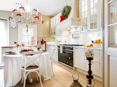Bazowa biel w kuchni z jadalnią piękne podkreśla czerwone świąteczne dodatki, jakie zastosowano w aranżacji. Klimat potęgują większe latarenki postawione na podłodze oraz wieniec na...