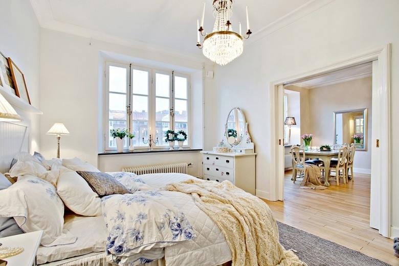Biała sypialnia łączy się szerokim przejściem z częścią dzienną mieszkania w kamienicy. Zaaranżowana w identycznym...