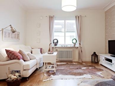 Biała sofa,zasłony,drewniany stolik kawowy i bydlęca skóra na podłodze w salonie (21921)