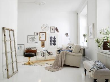 Skandynawskie grafiki,mapy i fotografie vintage w aranżacji białego salonu z dywanem ze skóry,pikowaną ławką i biała stylową sofą (24719)