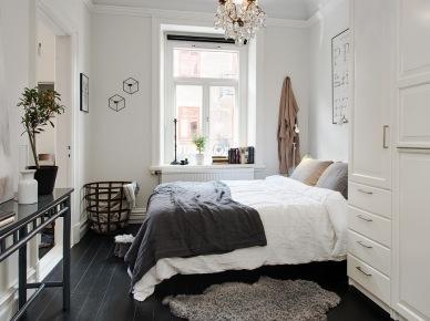 Francuski kryształowy zyrandol,czarna konsolka,metalowy ażurowy kosz i czarna podłoga z desek w aranżacji białej sypialni (25932)