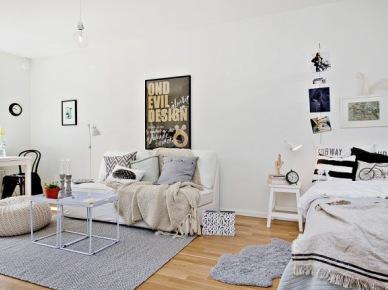 Czarno-białe poduszki na łóku stojącym w salonie z białymi stolikami,białą sofą i szarym dywanem (24697)