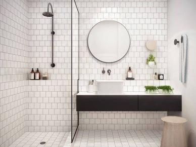 Biala płytka na ścianach i podłodze w małej łazience z wydzielonym murowanym brodzikiem,czarną armaturą łazienkową,czarnym okragłym lustrem i czarną wiszącą szafką z naszafkową umywalką (26033)