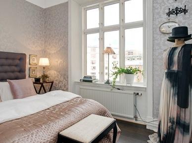 Szare pikowane łóżko w sypialni ze srebrną tapetą na ścianach (20379)