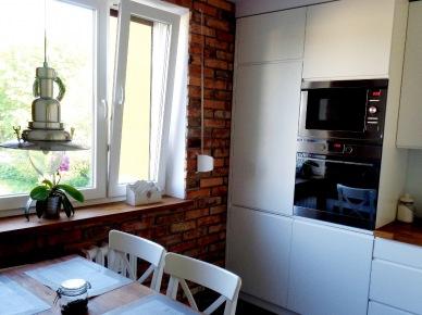Na jednej z kuchennych ścian postawiono na charakterystycznączerwoną cegłę. Elementem praktycznym, jak i mocno dekoracyjnym zarazem, jest również lampa...