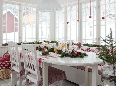 Aranżacja jadalni skąpana w śnieżnej bieli nawiązuje do sielskiego rustykalnego klimatu. Czerwone dodatki w świątecznym klimacie przygotowują do grudniowego święta. Choinka i pojedyncze gałązki świerku w subtelny sposób dekorują...