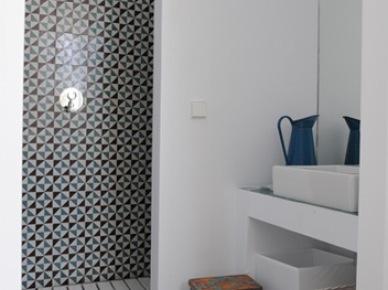 Murowane białe półki w łazience,drewniany ażurowy podest w kabinie,wzorzysta glazura w hiszpańskim stylu,stołek vintage,niebieskie metalowy dzban na wodę w śródziemnomorskiej łazience (26018)