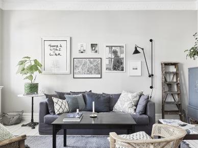 Dekoracja ściany współczesnymi grafikami nad szarą sofą w salonie,drewniana drabina w roli dekoracji salonu,czarny prostokatny stolik (47757)