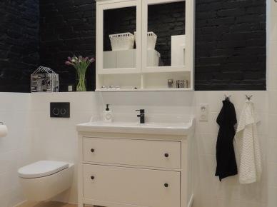 Białe, delikatne meble łazienkowe na tle czarnych cegieł. Czarno – białe dodatki w tym pomieszczeniu idealnie współgrają z całą...