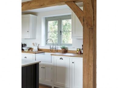 Białe meble w kuchni z drewnianym blatem i belkami (49018)