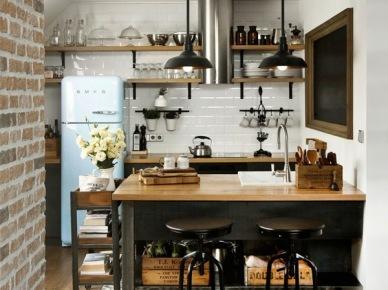 W aranżacji kuchni postawiono na zdecydowaną czerń oraz naturalne drewno, co w połączeniu z nieco surową formą niektórych loftowych dodatków tworzy efektowną i oryginalną mieszankę. Białe kafle na ścianie i błękitna lodówka łagodzą i jednocześnie równoważą nieco klimat...