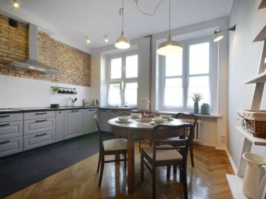 Wysokie pomieszczenie urządzono w lekko eklektycznym stylu. Kuchnię oraz jadalnię rozgranicza wyraźnie podłoga, poza tym obie strefy wnętrza spójnie do siebie nawiązują. W jadalni umieszczono piękne meble w drewna, w tym okrągły stolik, który w razie potrzeby może pomieścić więcej...