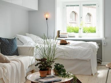 Białe wiszące szafki,łóżko przy oknie i biała sofa, okagłymetalowy stolik z tacą i etniczny brązowy dywan w salonie połączonym z sypialnią (25911)