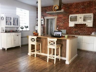 Aranżacja przestronnej kuchni z wygodną wyspą i charakterystycznymi cegłami na ścianie. Drewniana podłoga i drewniane elementy na wyspie kuchennej wzmacniają domowy ciepły klimat we...