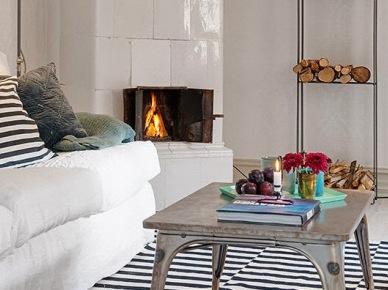 aż miło popatrzeć ! kolejny salon w stylu skandynawskim z industrialnymi dodatkami. Biały salon z ceramicznym piecem i mieszanką industrialnych dekoracji w odcieniach szarości, turkusu i czerni w prostej i czarującej aranżacji. Drewniana witryna i skórzany puf w brązowym kolorze ocieplają wnętrze i nadają mu przytulności. Skandynawski, znajomy design a zarazem odkrywczy i bardzo świeży ! Warto przyjrzeć się oprawie okna, która została pomysłowo wykorzystana na panel świetlny...