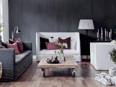 Luźne pokrowce z białego i szarego lnu na sofach w salonie z ciemnoszarą ścianą,drewnianą podłogą,stolikiem z palety na kółkach i zieloną choinką z białymi dekoracjami (47765)
