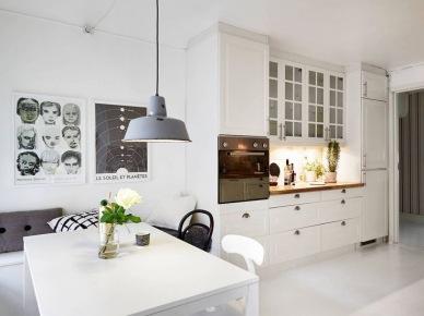 Biała kuchnia w stylu skandynawskim  w otwartym widoku z jadalnią z białym stołem i różnymi krzesłami (26583)