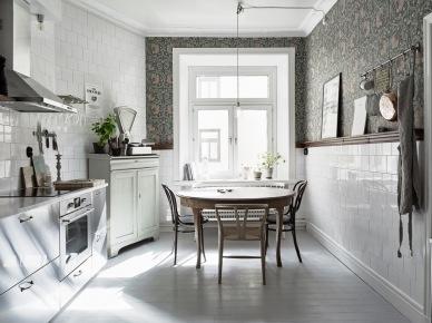 Okrągły drewniany stół w klasycznym stylu,miętowa drewniana komoda,stalowa uchnia,stylowa tapeta i białe ceramiczne płytki na ścianie w eklektycznej kuchni (47752)