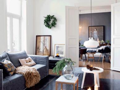 Szare lniane pokrowce na sofie w białym salonie,biały okragły stolik kawowy,zielone gałązki choinki w szklanym wazonie na drewnianym stoliku (47766)