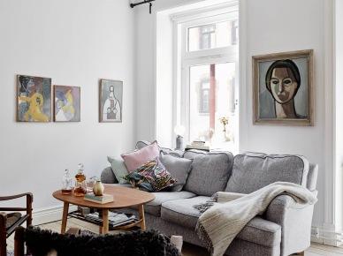 Kolorowe wspólczesne malarstwo w aranzacji białego salonu z szarą sofą i drewnianym okragłym stolikiem w stylu skandynawskim (25725)