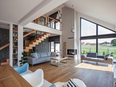 Okna na całą wysokość ściany zapewniają maksimum światła dziennego w salonie. Drewniana podłoga, schody czy stoły ocieplają wnętrze i świetnie współgrają z bazową...