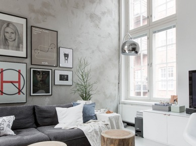 Nowoczesne fotografie i grafiki na betonowej ścianie,szara sofo modułowa,drewniane pieńki (47852)