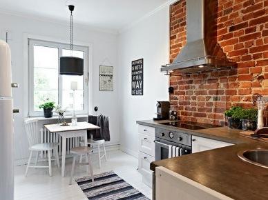 W kuchni czerwone cegły mogą stanowić także jedynie dodatek. Fragment ściany wyłożony naturalnym materiałem dostatecznie zwraca na siebie uwagę wśród śnieżnej...