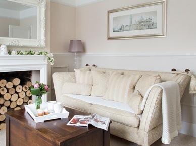 Biały stylowy kominek z klasyczną sofą i kolonialną skrzynią w roli stolikia (21724)