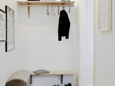 Drewniana podłoga i półki w małym przedpokoju,białe ściany,szara tapicerowana ławka,skandynawski biało-czarny dywanik (47831)