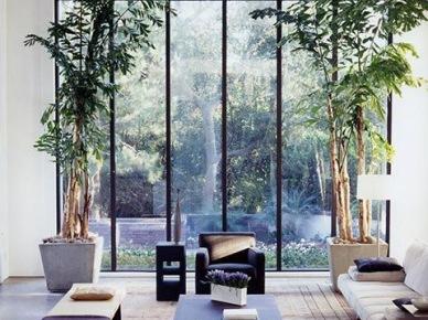 Szlana ściana podzielona stalowymi ramami w wysokim salonie z widokiem na ogród (47863)