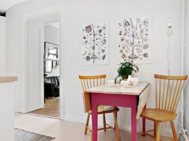 Botaniczne plakaty, różowy stół z drewnianym blatem i żarówka na kablu w dekoracji kuchni (25922)