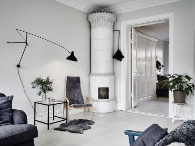 Biały ceramiczny piec w klasyczneym skandynawskim stylu,czarny kinkiet na wysięgniku,bielone deski z drewna na podłodze w salonie (47751)