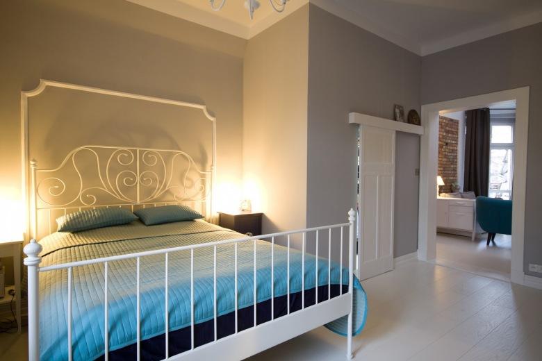 Aranżacja wysokiej sypialni czerpie z romantycznego stylu prowansalskiego. Metalowa rama łóżka w białym kolorze...
