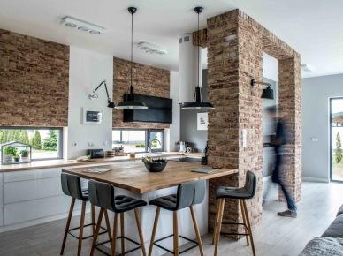 W wystroju kuchni postawiono na fragmenty z czerwonych cegieł również, np. na filarze czy na ścianachnad oknami. Zestawiono je z tak wyrazistymi elementami, jak meble czy dodatki w nasyconej czerni, co potęguje wyjątkowy charakter...