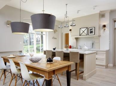 Aranżacja całkowicie otwartej kuchni połączonej z jadalnią za pomocą sporej wielkości wyspy kuchennej. Drewniany stół w jadalnianej części został urozmaicony czarnym kolorem na nogach, które przełamują jasną stonowaną przestrzeń. Białe krzesła w skandynawskim stylu zestawiono z dodatkami o klasycznym eleganckim...