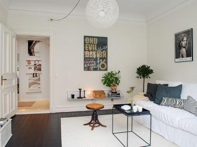 Czarne deski na podłodze w salonie,biala sofa,kulista ażurowa lampa,stylowy stołek i czarny stolik z tacą (25931)