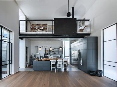 Dzięki wysokości domu możliwe było wyeksponowanie antresoli nad częścią kuchenną. Czarna balustrada swoim nasyconym kolorem dość mocno kontrastuje z dominującą szarością na palecie...