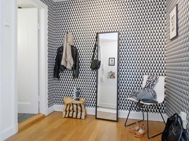 Czarne lustro stojace,skandynawska biało-czarna tapeta w trójkąty,białe krzsło na czarnych metalowych płozach,papierowa torba pojemnik na podłodze (25777)