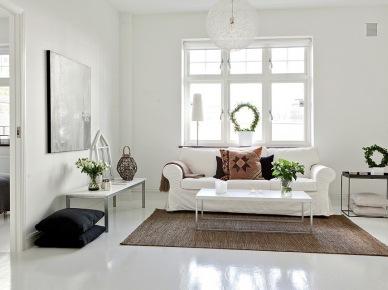 Biała sofa,jutowy dywan i czarne poduszki w salonie (18390)