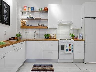 to nietypowe mieszkanie, bo ma specyficzny kształt, który zmusił właścicieli do urządzenia mieszkania nietypowo i bardzo oryginalnie. Aby w małym mieszkaniu pozostać przy otwartej zabudowie i zarazem stworzyć niezbędny klimat, to trzeba pomyśleć o umiejscowieniu łóżka na antresoli. Białe ściany i podłogi powiększają wizualnie całe mieszkanie, a dodatkowe, wolne metry powierzchni uzyskano dzięki wykonaniu nietypowej zabudowy - antresoli z łóżkiem. Mieszkanie zyskało nie tylko na metrażu, ale również na oryginalności. Typowo skandynawski wystrój mieszkania zdobią czarne detale - nowoczesny wieszak-drzewko, girlandy  ze świetlnymi kulami oraz sofa i pojedyncze krzesła. Kontrast nadał wnętrzu charakteru i ożywił białe ściany i...