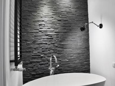 Czarny kamień łupek na scianie w łazience,biała owalna wanna wolnostojąca,czarny kinkiet nad wanną (26015)