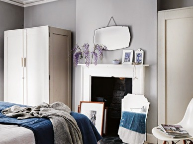 Szare ściany,dekoracyjne skandynawskie lustra,granatowa narzuta, i biała szafa w sypialni (25065)