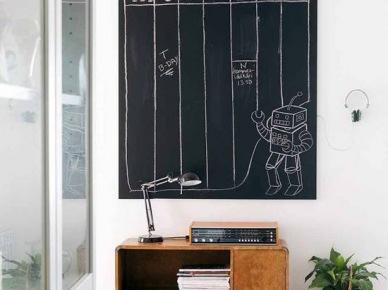 Przeszkolone szafy we wnęce,czarna tablica nabiałej  ścianie, drewniana szafka pezy ścianie,szara metalowa walizka na podłodze w przedpokoju (25791)