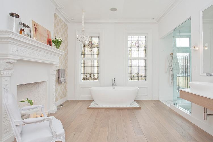 Biały pokój kąpielowy ze stylowym kominkiem,owalną wanną i drewniana podłogą