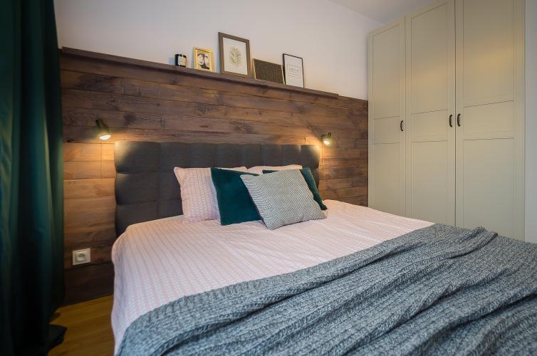 Polska aranżacja przytulnego mieszkania z otwartą kuchnią i drewnianą ścianą w sypialni