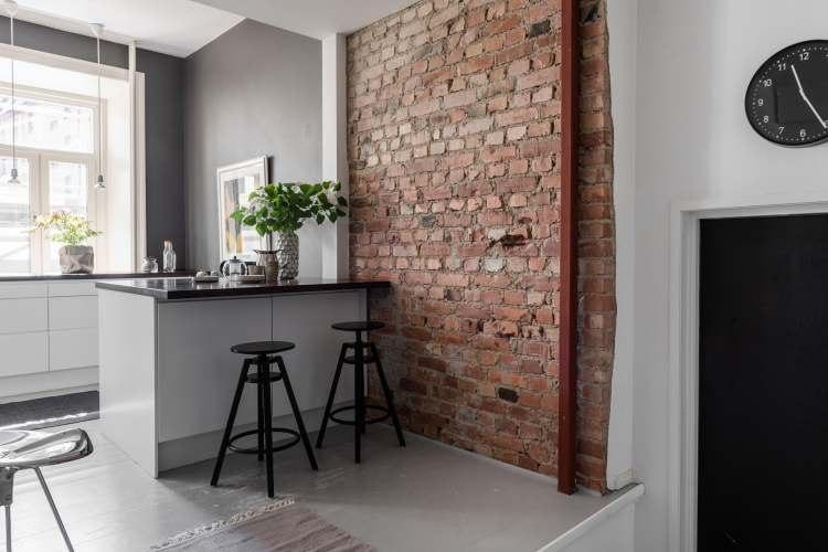 Aranżacja przestronnego mieszkania w kamienicy z kuchnią z czerwonymi cegłami