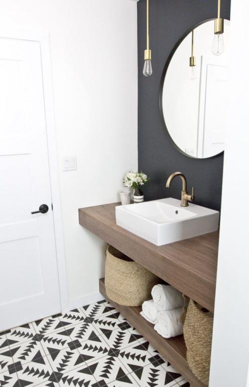 Before & after małej łazienki ze wzorzystą podłogą, czarną ścianą i złotymi dodatkami