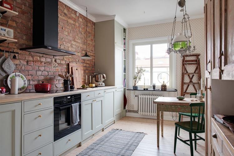 Aranżacja mieszkania z przestronną kuchnią z czerwonymi cegłami w eklektycznym stylu