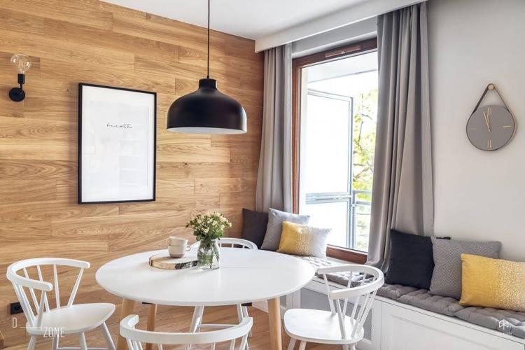 Inspirująca aranżacja mieszkania z białą kuchnią i drewnianą ścianą w jadalni!