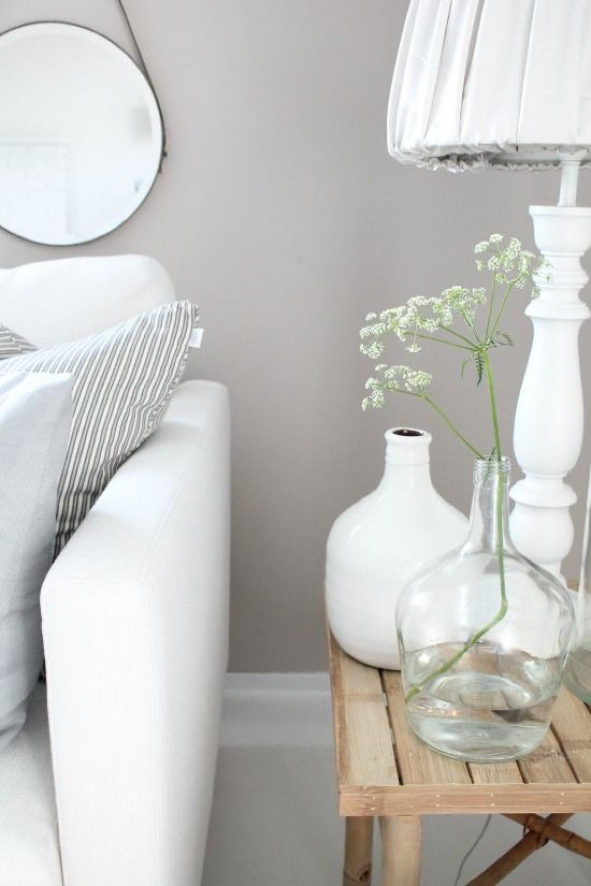 Szara ściana,okragłe wiszące lustro na rzemyku,biała sofa,biała
